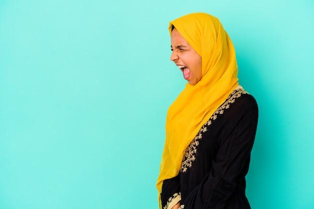 Jonge moslimvrouw die op blauwe achtergrond wordt geïsoleerd die naar een exemplaarruimte schreeuwt