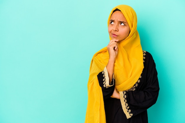 Jonge moslimvrouw die op blauwe achtergrond wordt geïsoleerd die zijwaarts met twijfelachtige en sceptische uitdrukking kijkt.