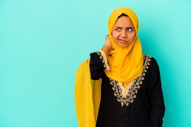 Jonge moslimvrouw die op blauwe muur wordt geïsoleerd die achterkant van het hoofd raakt, denkt en een keuze maakt.