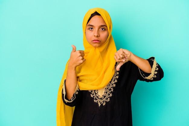 Jonge moslimvrouw die op blauwe muur wordt geïsoleerd die duimen omhoog en duimen omlaag toont, moeilijk kiest concept