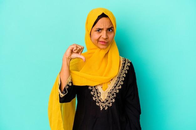 Jonge moslimvrouw die op blauwe muur wordt geïsoleerd die een afkeergebaar toont, duimen naar beneden