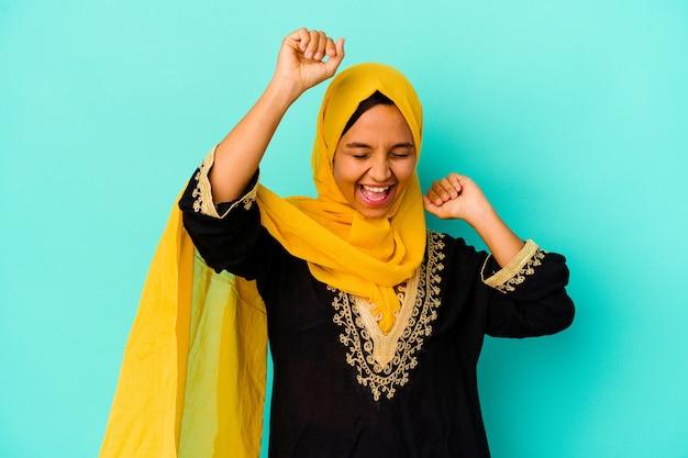 Jonge moslimvrouw die op blauwe muur wordt geïsoleerd die een speciale dag viert, springt en heft wapens op met energie