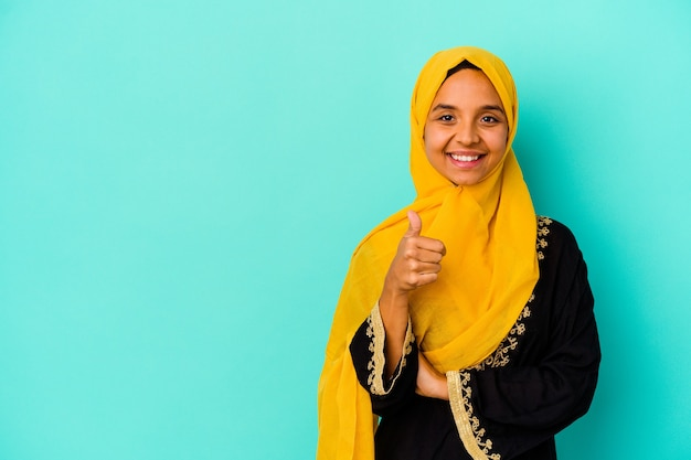 Jonge moslimvrouw die op blauwe muur wordt geïsoleerd die en duim opheft