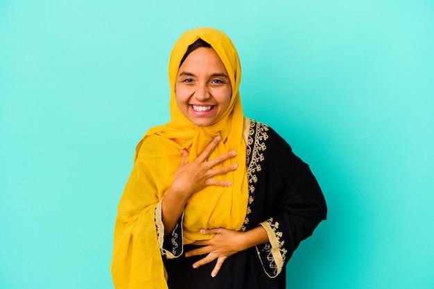 Jonge moslimvrouw die op blauwe muur wordt geïsoleerd die en pret lacht heeft