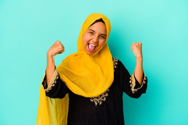 Jonge moslimvrouw die op blauwe muur wordt geïsoleerd die krachtgebaar met wapens, symbool van vrouwelijke macht toont