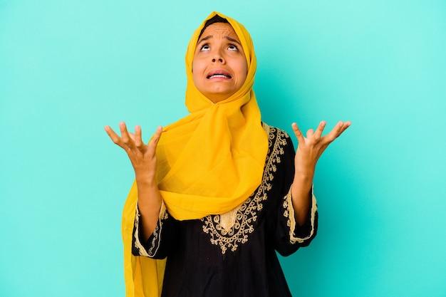 Jonge moslimvrouw die op blauwe muur wordt geïsoleerd die naar de hemel schreeuwt, omhoog kijkt, gefrustreerd.