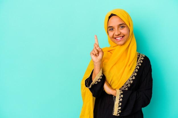 Jonge moslimvrouw die op blauwe muur wordt geïsoleerd die nummer één met vinger toont.