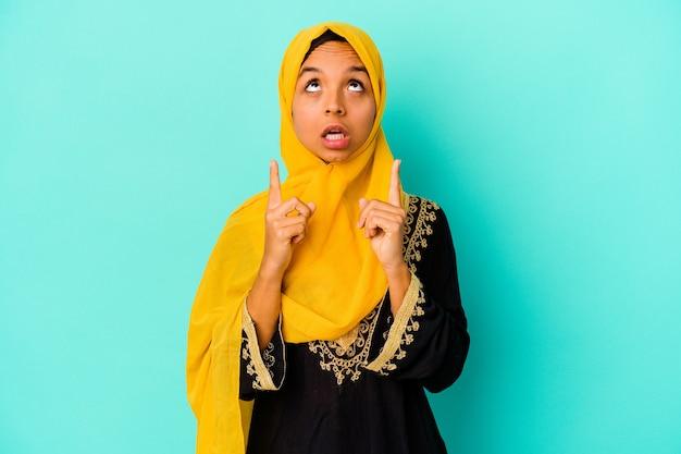 Jonge moslimvrouw die op blauwe muur wordt geïsoleerd die ondersteboven met geopende mond richt
