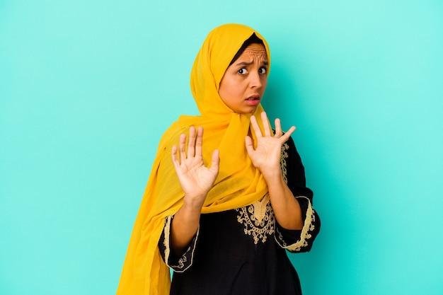 Jonge moslimvrouw die op blauwe muur wordt geïsoleerd die wegens een dreigend gevaar wordt geschokt