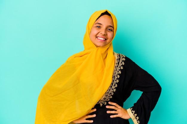 Jonge moslimvrouw die op blauwe muur wordt geïsoleerd die zelfverzekerd handen op heupen houdt