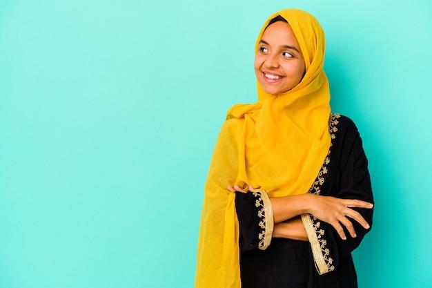 Jonge moslimvrouw die op blauwe muur wordt geïsoleerd die zelfverzekerd met gekruiste armen glimlacht