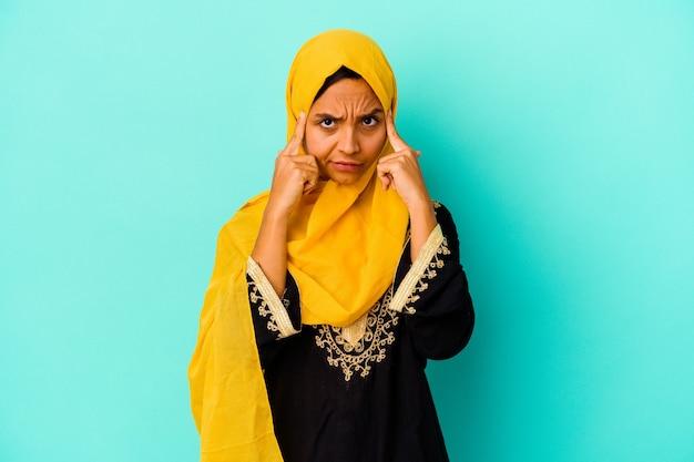 Jonge moslimvrouw die op blauwe muur wordt geïsoleerd die zich op een taak concentreert, met wijsvingers die het hoofd richten.