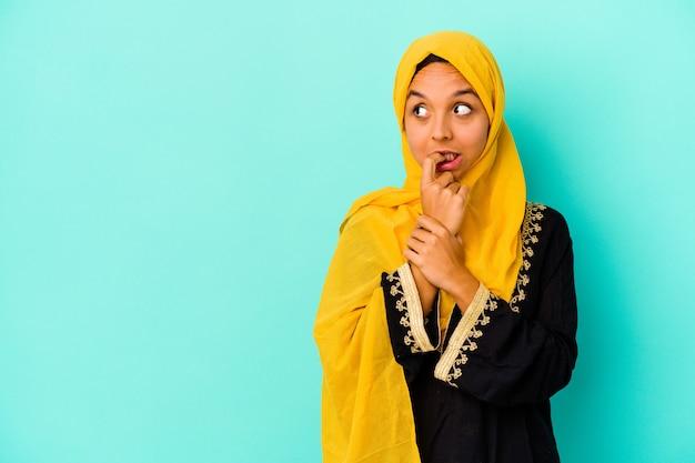 Jonge moslimvrouw die op blauwe muur wordt geïsoleerd ontspant denkend over iets dat een exemplaarruimte bekijkt