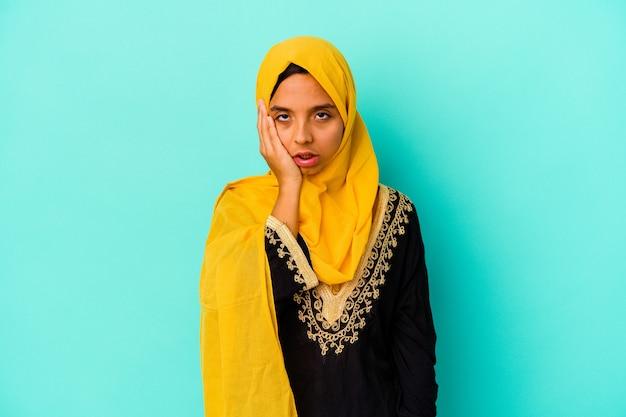 Jonge moslimvrouw die op blauwe muur wordt geïsoleerdmoe en zeer slaperig die hand op hoofd houdt.