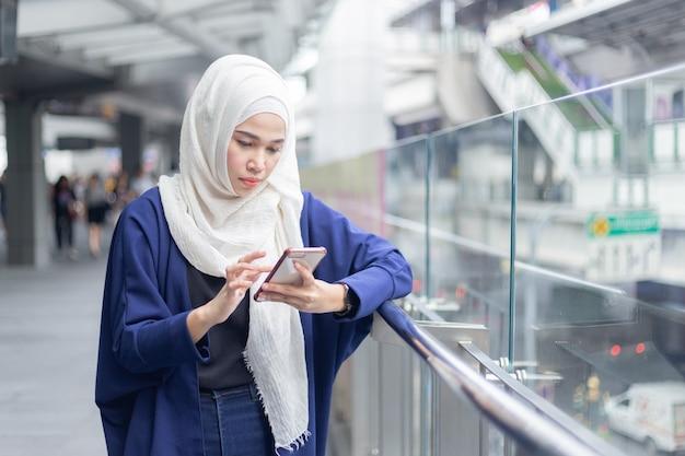 Jonge moslimvrouw die smartphone gebruikt.