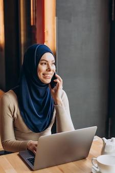 Jonge moslimvrouw die telefoon gebruikt en aan computer in een café werkt