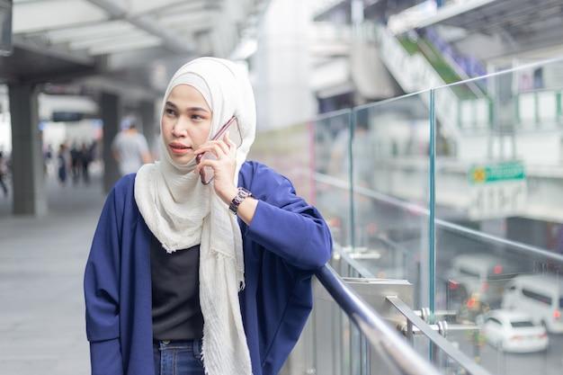 Jonge moslimvrouw die telefoon met behulp van