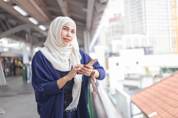 Jonge moslimvrouw die telefoon op skytrainpost met behulp van.