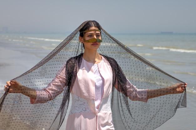 Jonge moslimvrouw draagt gouden masker, hormozgan, iran.