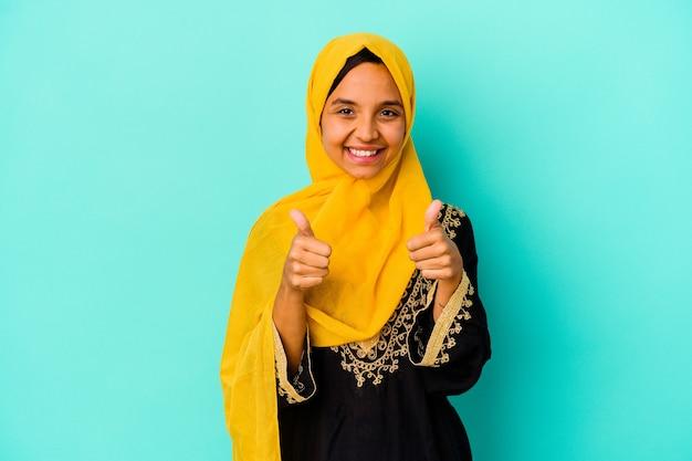 Jonge moslimvrouw geïsoleerd op blauwe muur met thumbs ups, proost over iets, steun en respect concept.