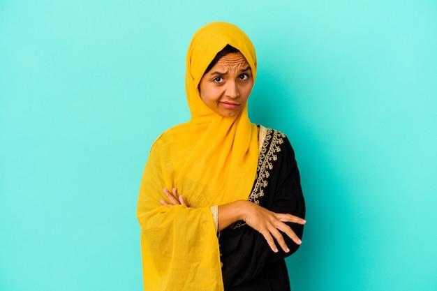 Jonge moslimvrouw geïsoleerd op blauwe muur ongelukkig in de camera kijken met sarcastische uitdrukking