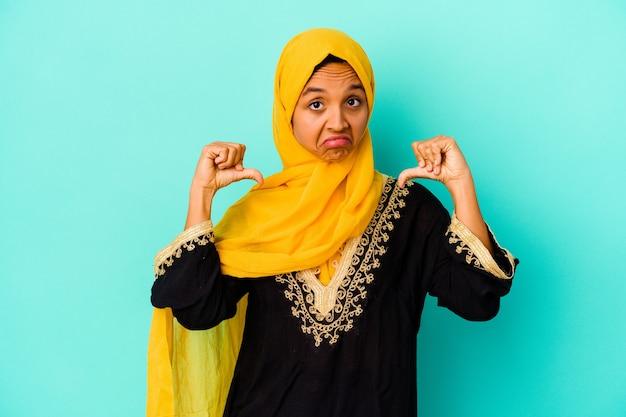 Jonge moslimvrouw geïsoleerd op blauwe muur voelt zich trots en zelfverzekerd, voorbeeld om te volgen.