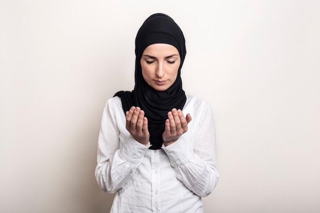 Jonge moslimvrouw gekleed in een wit overhemd en hijab bidden