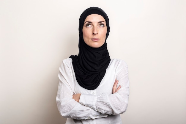 Jonge moslimvrouw gekleed in een wit overhemd en hijab heeft haar armen gekruist en wordt opgezocht