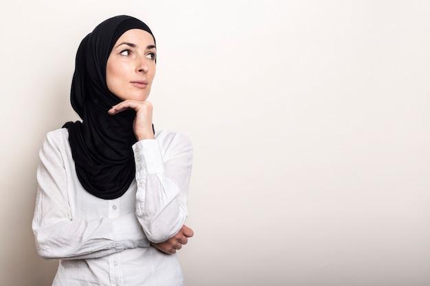 Jonge moslimvrouw gekleed in een wit overhemd en hijab houdt haar hand tegen haar kin en kijkt opzij