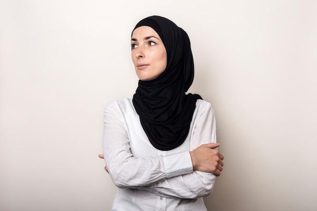 Jonge moslimvrouw gekleed in een wit overhemd en hijab kijkt naar de zijkant
