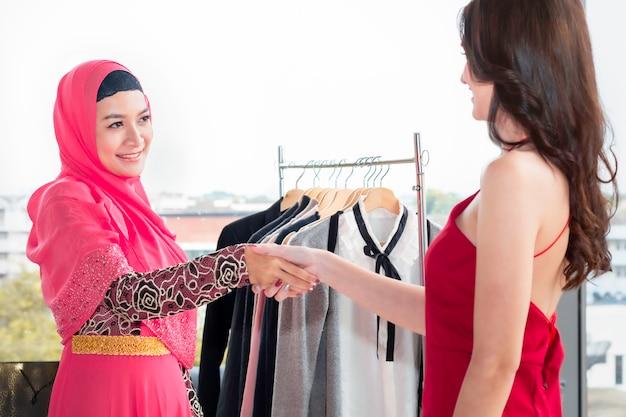 Jonge moslimvrouw het schudden hand met kaukasische vriendschappen die dichtbij het winkelen zakken zitten
