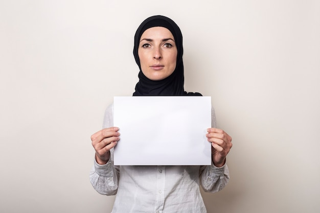 Jonge moslimvrouw in een wit overhemd en hijab houdt een blanco vel papier vast