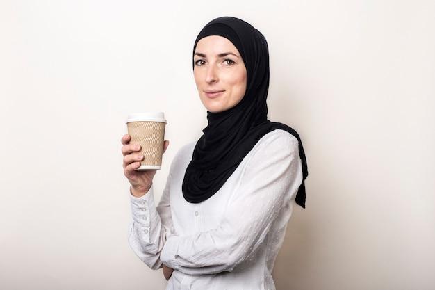Jonge moslimvrouw in een wit overhemd en hijab met een glimlach houdt een papieren beker met koffie