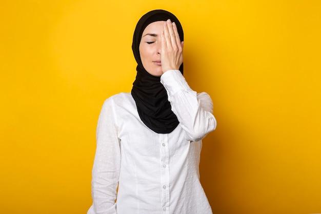 Jonge moslimvrouw in hijab bedekt de helft van haar gezicht met haar handpalm op een gele