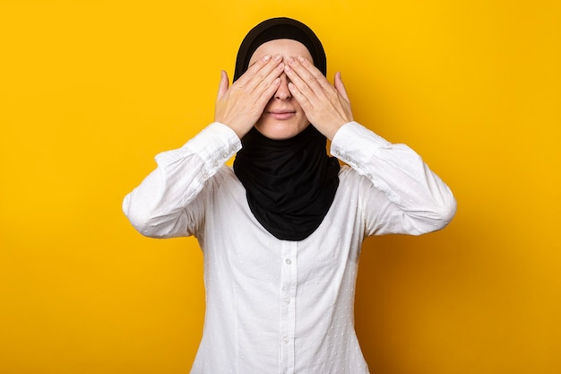 Jonge moslimvrouw in hijab bedekte haar ogen met haar handen op een geel