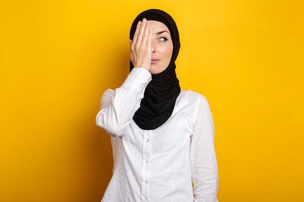 Jonge moslimvrouw in hijab die één oog bedekt met haar hand glimlacht en kijkt opzij op geel