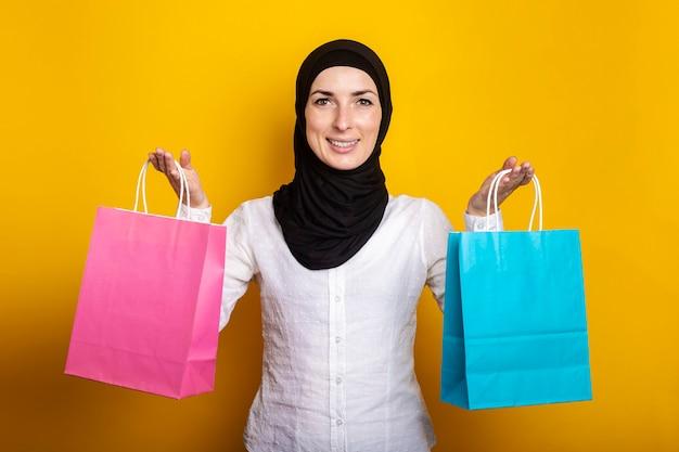 Jonge moslimvrouw in hijab glimlacht en houdt boodschappentassen op geel