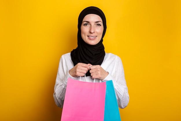 Jonge moslimvrouw in hijab glimlacht en houdt boodschappentassen