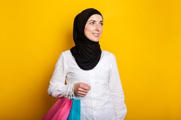 Jonge moslimvrouw in hijab glimlacht, kijkt opzij en houdt boodschappentassen op een gele