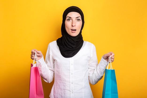 Jonge moslimvrouw in hijab houdt boodschappentassen met verbaasd gezicht op geel