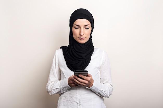 Jonge moslimvrouw in hijab houdt een telefoon in haar handen en kijkt ernaar