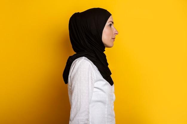 Jonge moslimvrouw in hijab kijkt naar de zijkant op een geel