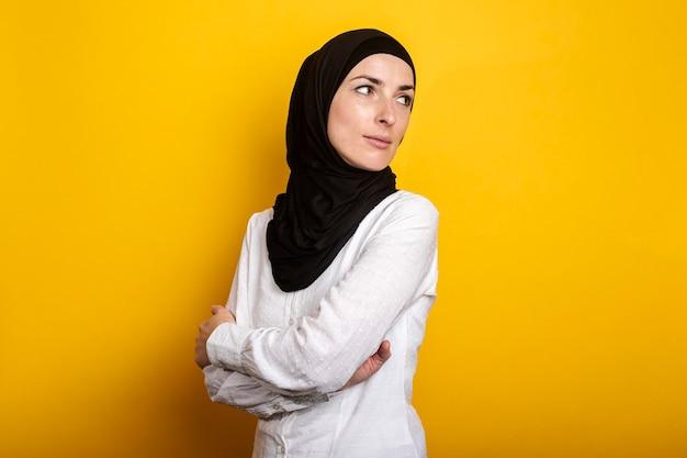 Jonge moslimvrouw in hijab kijkt opzij en kijkt terug tegen een gele