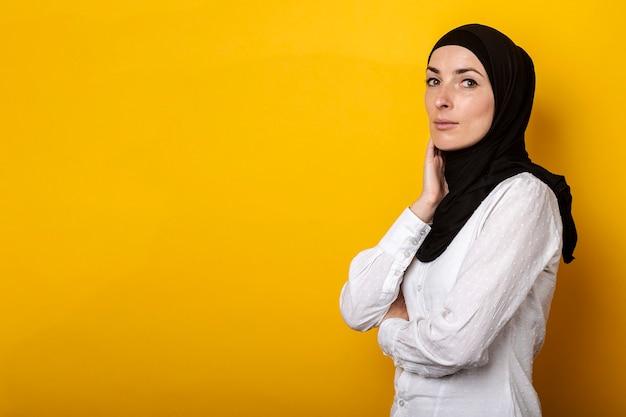 Jonge moslimvrouw in hijab lachend op een geel