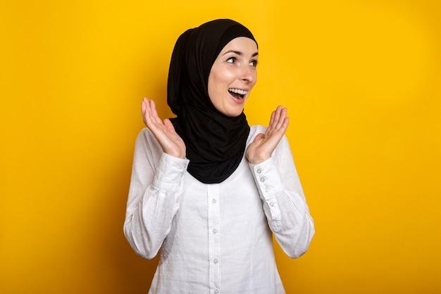 Jonge moslimvrouw in hijab met een verbaasd gezicht op geel