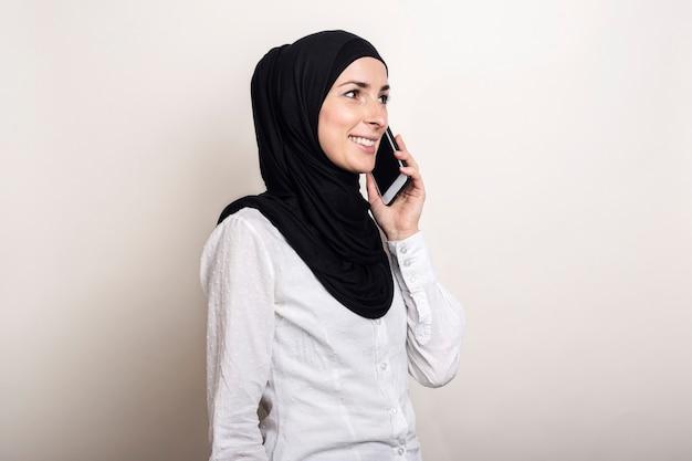 Jonge moslimvrouw in hijab praten aan de telefoon en op zoek naar de zijkant