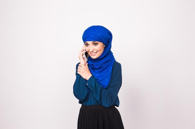 Jonge moslimvrouw in hoofddoek die telefoon met behulp van.