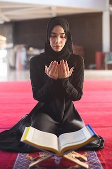 Jonge moslimvrouw in slijtage zwarte kleding die met koran in moskee bidden.