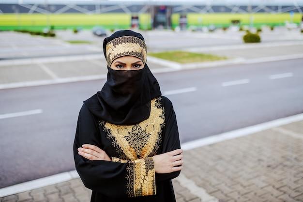 Jonge moslimvrouw in traditionele slijtage die zich buiten met gekruiste wapens bevindt.