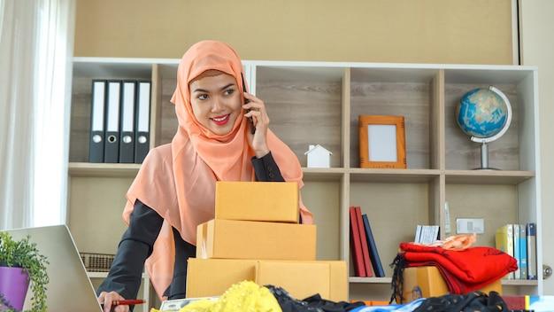 Jonge moslimvrouw, kleine bedrijfseigenaar die thuis werkt